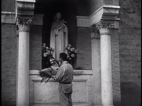 male placing flowers at base of st theresa of the andes statue front rear of casino of pius iv - state of the vatican city stock videos & royalty-free footage