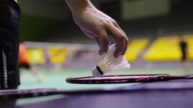 vidéos et rushes de joueur mâle ramassant la raquette de badminton avec des volants. - badminton sport