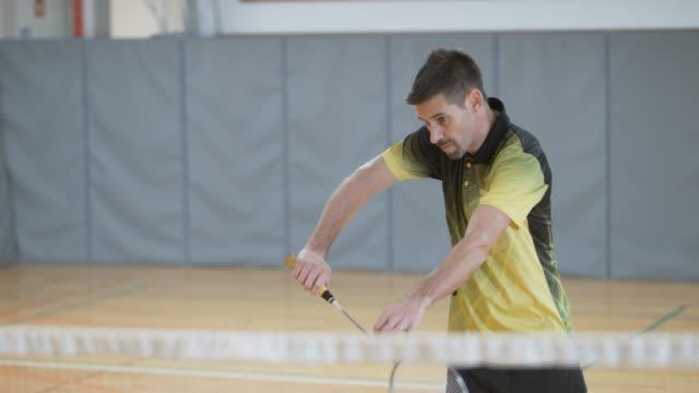 vídeos de stock, filmes e b-roll de masculino jogador jogando badminton indoor - badmínton esporte