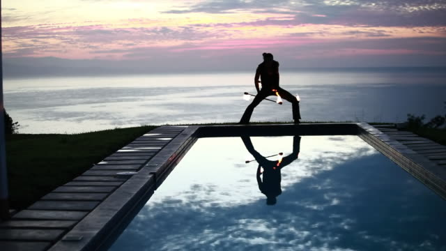 ws male poi dancer performing in front of pool with reflection of his silhouette in pool at sunrise / montezuma, costa rica - kelly mason videos bildbanksvideor och videomaterial från bakom kulisserna