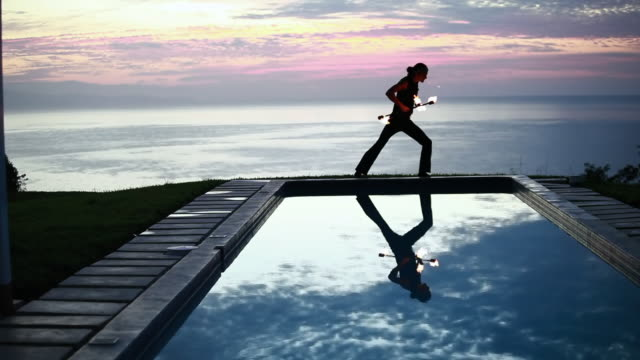 vidéos et rushes de ws male poi dancer performing in front of pool with reflection of his silhouette in pool at sunrise / montezuma, costa rica - kelly mason videos