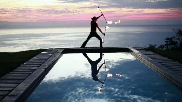 vídeos de stock e filmes b-roll de ws male poi dancer performing in front of pool with reflection of his silhouette in pool at sunrise / montezuma, costa rica - braço humano