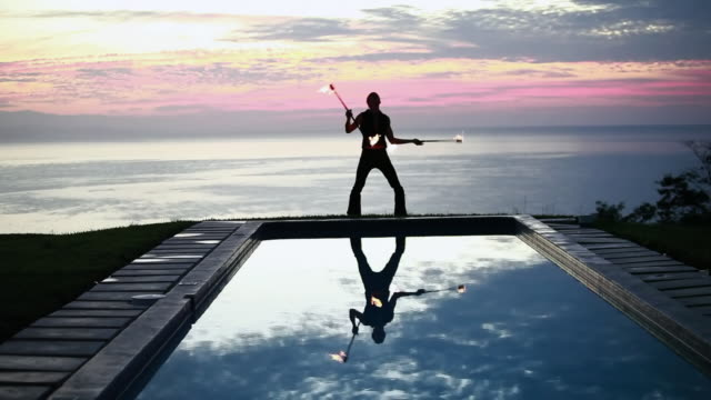 ws male poi dancer performing in front of pool with reflection of his silhouette in pool at sunrise / montezuma, costa rica - kelly mason videos stock videos & royalty-free footage