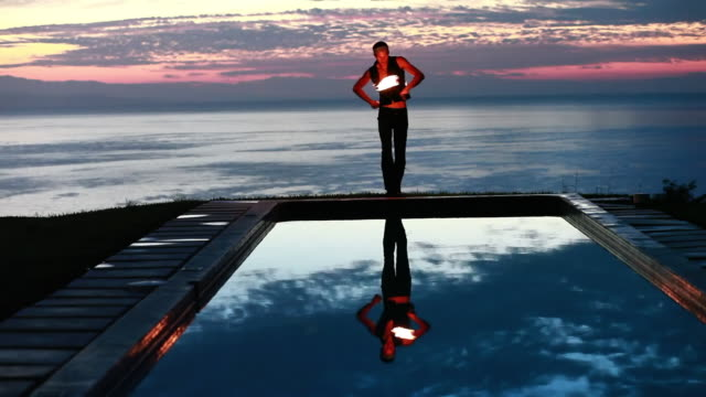 ws male poi dancer performing with fireballs in front of pool with reflection of his silhouette in pool at sunrise / montezuma, costa rica - kelly mason videos stock videos & royalty-free footage