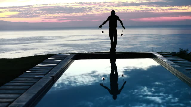 ws male poi dancer performing with fireballs in front of pool with reflection of his silhouette in pool at sunrise / montezuma, costa rica - kelly mason videos stock-videos und b-roll-filmmaterial