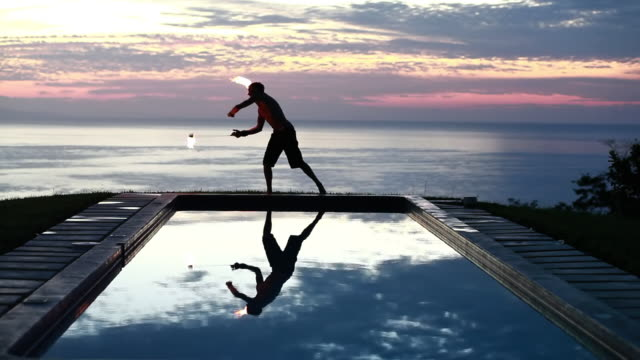 stockvideo's en b-roll-footage met ws male poi dancer without shirt performing with fireballs in front of pool with reflection of his silhouette in pool at sunrise / montezuma, costa rica - kelly mason videos