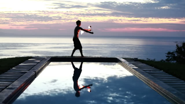 vidéos et rushes de ws male poi dancer without shirt performing with fireballs in front of pool with reflection of his silhouette in pool at sunrise / montezuma, costa rica - kelly mason videos