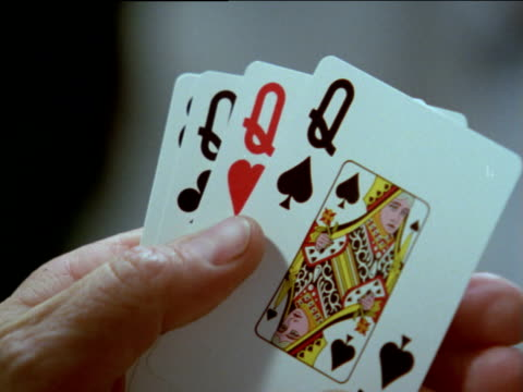 vídeos de stock, filmes e b-roll de male poker player fans out hand of cards, revealing four queens and an eight - pôquer