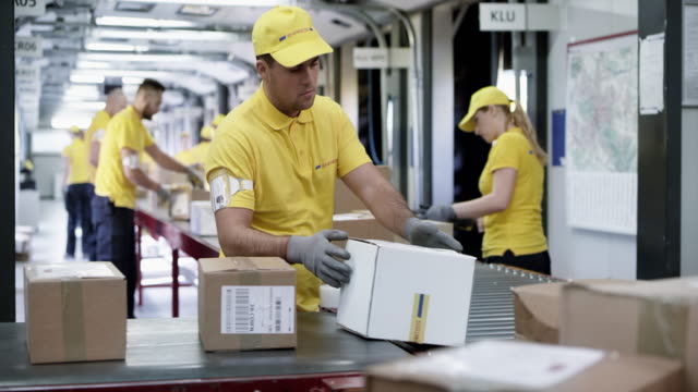 ds männlich postarbeiter sortieren von paketen auf dem förderband - arbeitsintensive produktion stock-videos und b-roll-filmmaterial