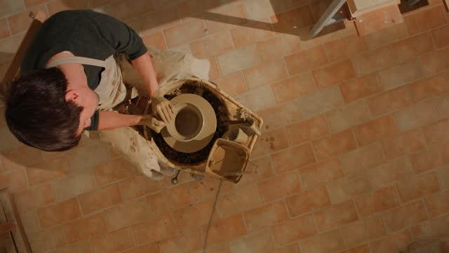 vidéos et rushes de potier mâle de cs créant un bol sur la roue du potier filature - poterie