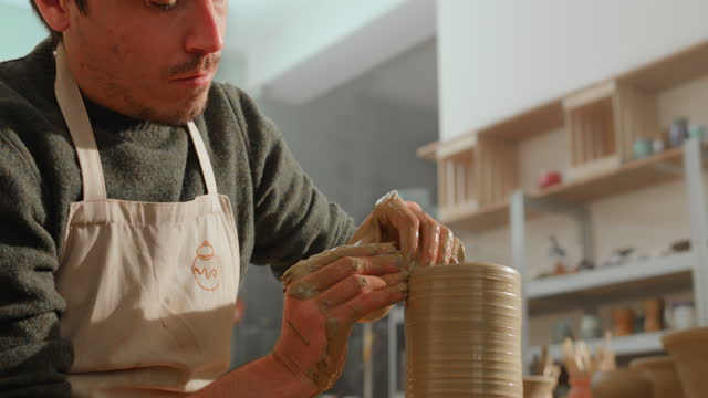 ds 車輪の上で回転する花瓶の壁を上げる男性陶芸家 - 陶芸家点の映像素材/bロール