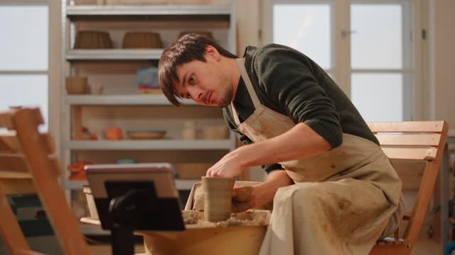 ds スタジオでポットを作っている間、ビデオチュートリアルを見て男性の陶芸家 - 陶芸家点の映像素材/bロール