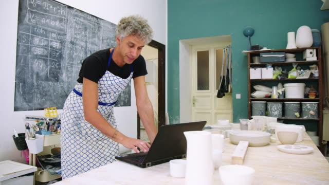 männliche keramik-künstler mit laptop in kunststudio - laptop benutzen stock-videos und b-roll-filmmaterial