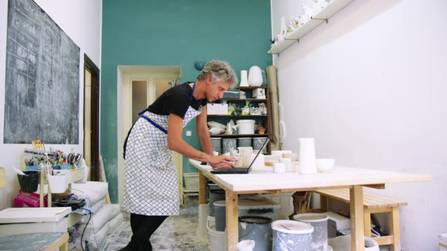male pottery artist using laptop in his workshop - hobbies stock videos & royalty-free footage
