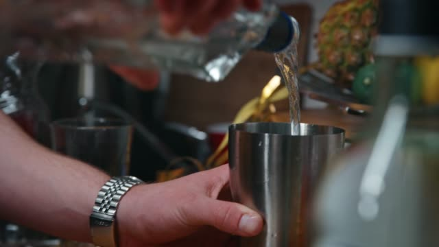 male pouring drink in glass from bottle at kitchen - scodella video stock e b–roll