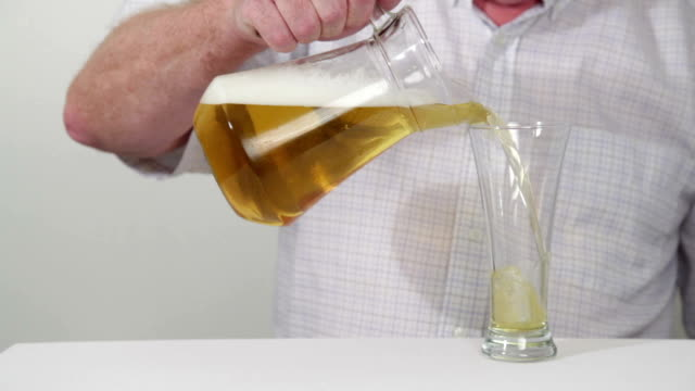 male pours half pint beer from pitcher into glass - pitcher jug stock videos & royalty-free footage