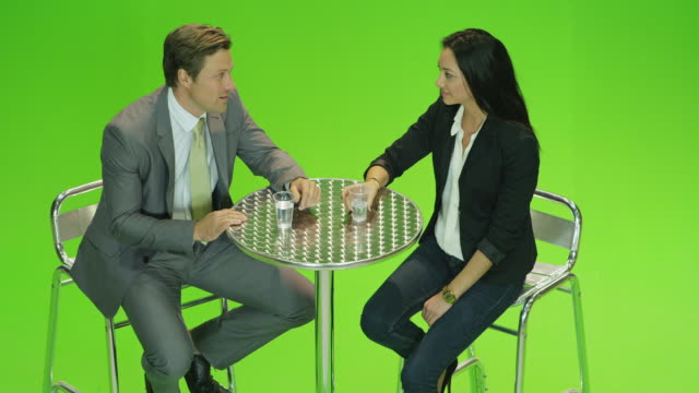 ha ms male presenter and female guest sitting on stools in front of green screen in tv studio, chatting - stool stock videos & royalty-free footage
