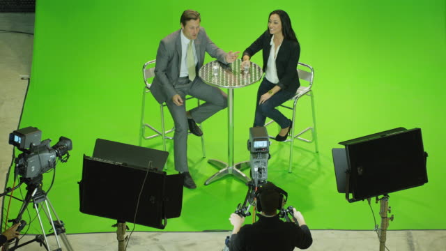 ha ws male presenter and female guest sitting on stools in front of green screen in tv studio, chatting, camera crew silhuetted in foreground - television studio stock videos & royalty-free footage