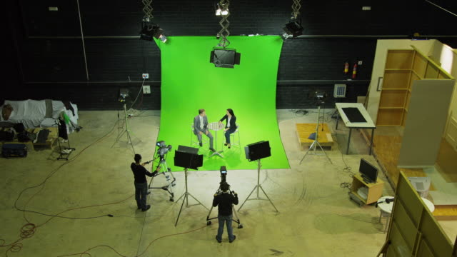 ha ews male presenter and female guest sitting on stools in front of green screen in tv studio, chatting, camera crew silhuetted in foreground - presenter stock videos and b-roll footage