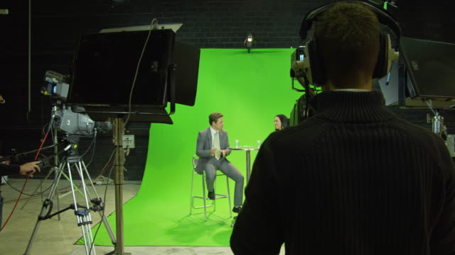 WS DS male presenter and female guest sitting on stools in front of green screen in TV studio, chatting, camera crew  in foreground