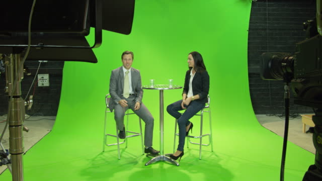 ws pan male presenter and female guest sitting on stools in front of green screen in tv studio, chatting, lights and stands visible in foreground - presenter stock videos & royalty-free footage