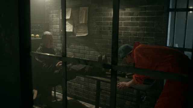 Male prisoner cleaning table in jail thru window