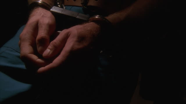 ECU, SLO MO, Male prisoner in chains walking, (close-up of hands)
