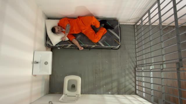 vídeos y material grabado en eventos de stock de 4k antena: hombre preso en cárcel tring para dormir - preso