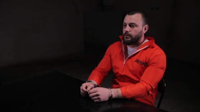 male prisoner in orange jumpsuit sitting alone in interrogation room - prisoner orange stock videos & royalty-free footage
