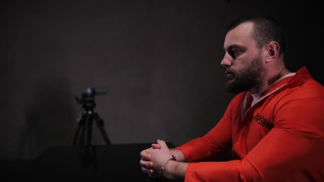 male prisoner in sitting alone in interrogation room - prisoner orange stock videos & royalty-free footage