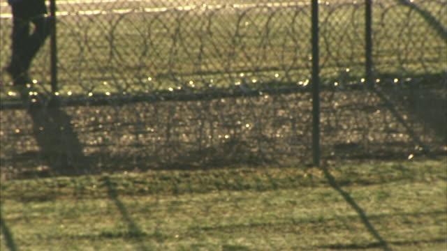 male prisoner legs lower torso walking alone along maximum security prison yard fence wrapped w/ razor wire fg incarceration not jail correctional... - gefängniszelle stock-videos und b-roll-filmmaterial