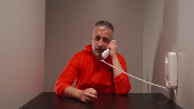 vídeos de stock, filmes e b-roll de homem prisioneiro falando ao telefone na sala de visitas da prisão - à prova de balas