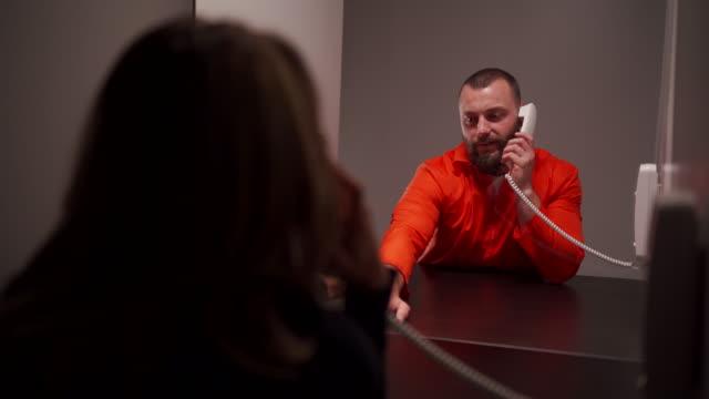 vídeos de stock, filmes e b-roll de homem prisioneiro falando com sua esposa triste na sala de visitas da prisão - à prova de balas