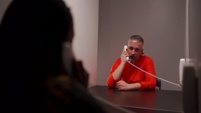 vídeos de stock, filmes e b-roll de homem prisioneiro falando com sua esposa na sala de visitas da prisão - à prova de balas