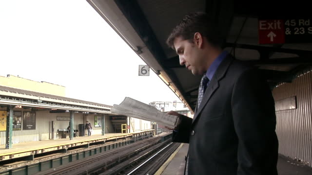 male professional reading newspaper on platform while waiting for train / looking up as train pulls up to platform / boarding train - number 6 stock videos & royalty-free footage