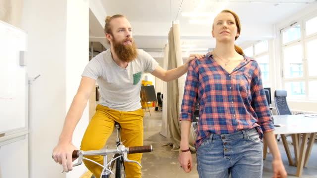 vidéos et rushes de homme professionnel équitation de vélo par un collègue - jeune pousse