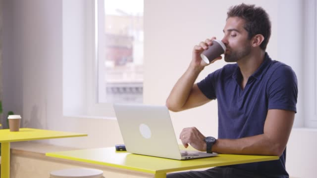 male professional sitting with coffee and laptop - three quarter length stock videos & royalty-free footage