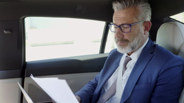 male professional working while traveling in car - reading glasses stock videos & royalty-free footage