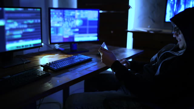 male programmer working on desktop computer at desk in office in dark - geek stock videos and b-roll footage