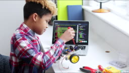 Male Pupil Building Robot Car In Science Lesson