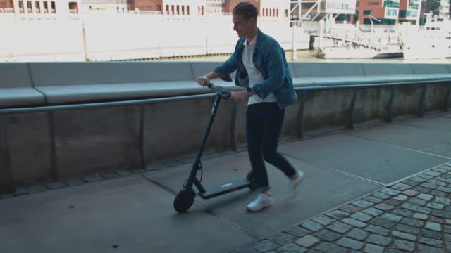 männchen schiebt elektro-push-scooter auf fußweg - pushing stock-videos und b-roll-filmmaterial