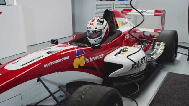 male racer sitting in red racing car at laboratory - casco da motociclista video stock e b–roll