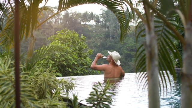 vidéos et rushes de détendant mâle à la piscine - bali