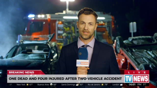 Male reporter reporting from the scene of a car accident
