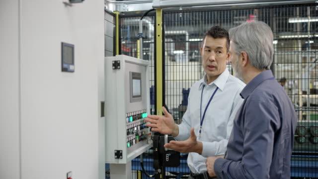 工場機械のオペレーターにアドバイスを与える産業機械製造会社の男性の代表者 - 説明する点の映像素材/bロール