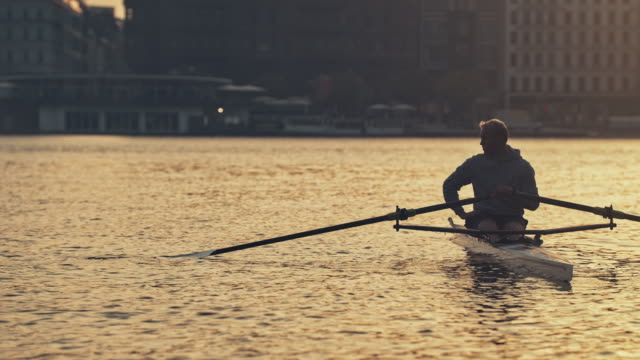 male resting on rowboat in river at sunset - sculling video stock e b–roll
