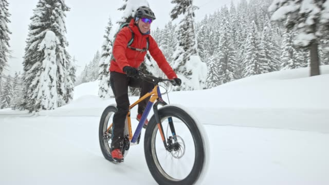 ts male rider enjoying fat biking on a snowy forest trail in winter - cycling helmet stock videos & royalty-free footage