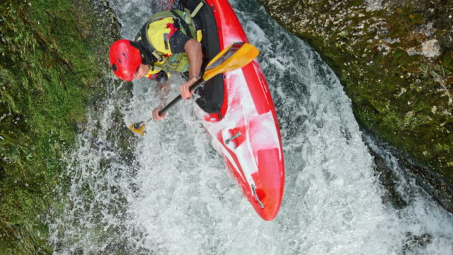 SLO MO Male rider running a waterfall in a red kayak