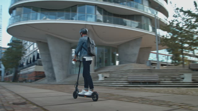 male riding electric kick scooter in city - motorino video stock e b–roll