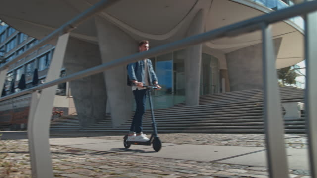männlich fahren elektro-kick-scooter auf fußweg - verkehrsweg stock-videos und b-roll-filmmaterial